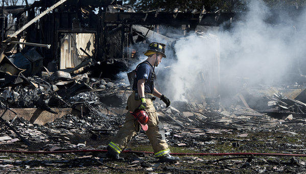 A firefighter walks across the rubble of a Knights of Columbus Hall in Bryan, Texas, after a blaze Friday night that killed two firefighters.