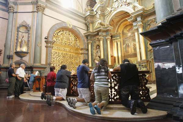 People pray while attending mass at the Nazarenas church in Lima February 16, 2013.