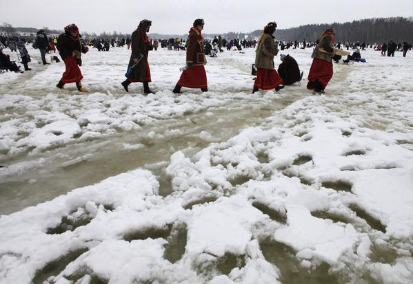 People in costumes walk during a traditional ice fishing competition on a lake near Viljandi February 16, 2013. Several thousand fishing lovers took part in the event to try to catch 130 marked fishes to win prize money.