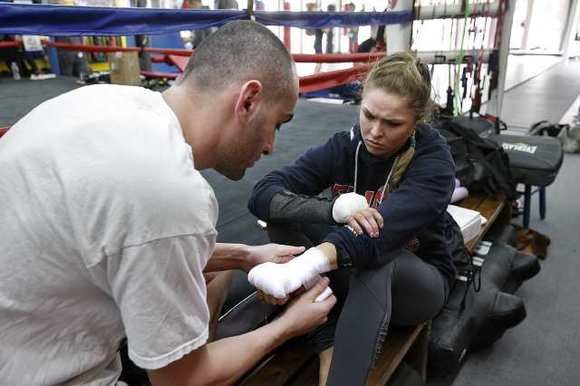 UFC Champion Ronda Rousey gets her hands wrapped by her trainer Edmond Tarverdyan before a training session at the Glendale Fighting Club.