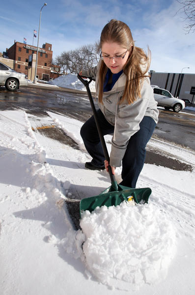 Brittany Sutton of Aberdeen Chiropractic demonstrates a snow shoveling technique. Sutton recommends lifting from your knees and moving small loads of snow at a time as ways to reduce back injury. American News Photo by John Davis