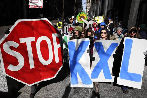 About 200 activists march around the Ralph H. Metcalfe Federal Building to protest the building of the Keystone XL Pipeline.