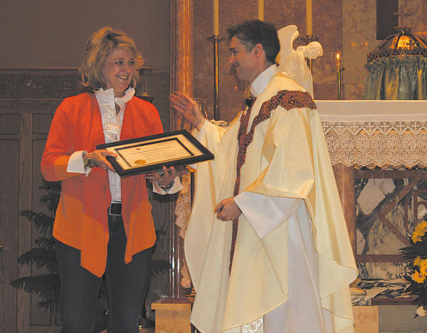 Kathleen Muldowney Murray is congratulated for being named St. Mary Catholic School Distinguished Graduate of 2013 by the Rev. J. Collin Poston, pastor of St. Mary  Catholic Church in Hagerstown.