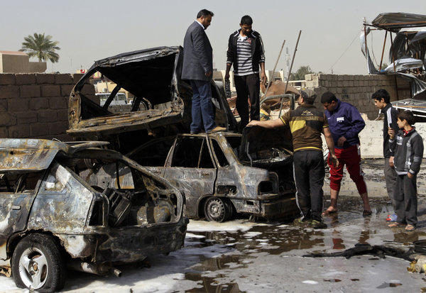 Destroyed cars litter the scene of a car bomb attack Sunday in the Ameen neighborhood of eastern Baghdad. A series of car bombs exploded within minutes of each other as Iraqis were out shopping in and around Baghdad, killing as many as 28 people.