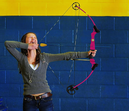 Clear Spring Middle School archer Catherine Kinman giggles while listening to friendly teasing from her peers Wednesday during practice in the school gymnasium. The team is preparing for a state tournament.