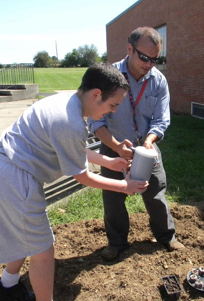 Franklin Learning Center student Justin Landaverde, left, and teacher Ken Decker work in a garden last year at the school outside Chambersburg, Pa.