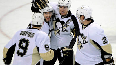 Pittsburgh Penguins Pascal Dupuis (9), Kris Letang (58) Sidney Crosby (87) and Matt Niskanen (2) celebrate the tying goal by Dupuis against the Buffalo Sabres during the third period of an NHL hockey game in Buffalo, N.Y., Sunday.