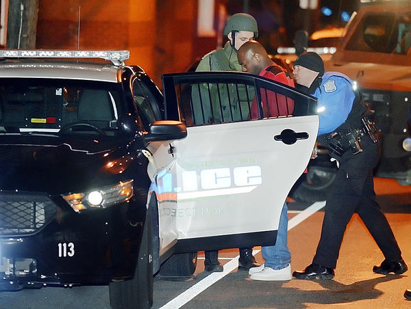 Hagerstown City Police Officers William Decker, right, and Sgt. John Lehman put Jenerette Dixon into a squad car after a standoff Saturday evening on Jonathan Street.