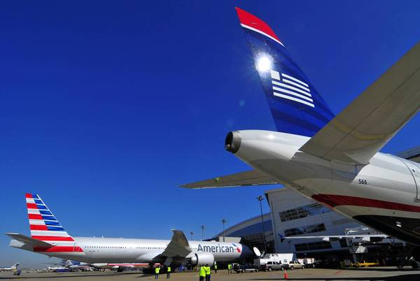 The $11-billion deal to merge American Airlines and US Airways would create the world's largest airline, employing more than 100,000 workers and serving about 187 million passengers a year. Above, US Airways and American jets at Dallas/Fort Worth International Airport in Fort Worth, Texas.