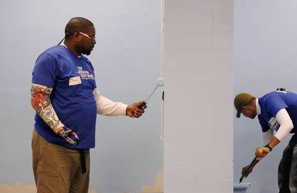 Army veteran Anthony Smith, left, and Marine Corps veteran Jaime Magallanes paint the cafeteria at the Dream Center in Echo Park as part of an event with the Mission Continues.