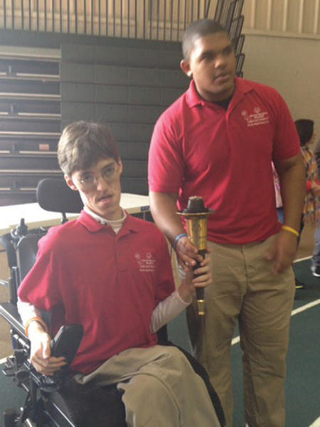 North Hagerstown bocce athletes Adam Barnhart, seated, and Trey King carried the opening ceremony torch to officially start the tournament at HCC.
