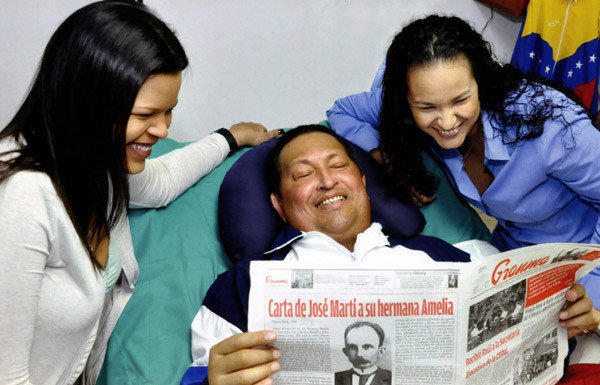 A picture released Friday by the Venezuelan presidential press office shows President Hugo Chavez flanked by daughters Maria, left, and Rosa and holding the Cuban newspaper Granma in Havana.