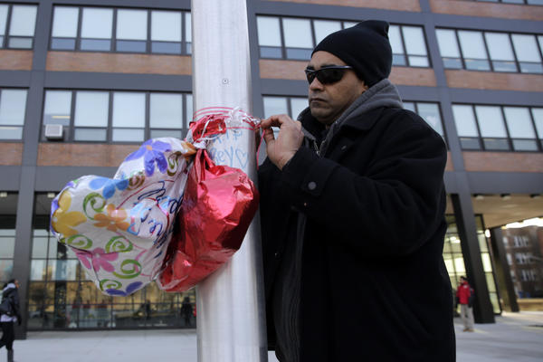 Jose Colon ties balloons to the flagpole outside Roberto Clemente High School in remembrance of his 18-year-old daughter, Frances Colon, who was shot and killed Friday night. Colon was the third student from Clemente killed this year.