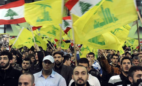 Lebanese supporters of Hezbollah wave Lebanese and Hezbollah flags in a Beirut suburb as they listen to leader Hassan Nasrallah deliver a speech via video link from an undisclosed location on Saturday. Several Hezbollah fighters were reported killed in Syria over the weekend in the latest indication of support by the Lebanese group for embattled Syrian President Bashar Assad.