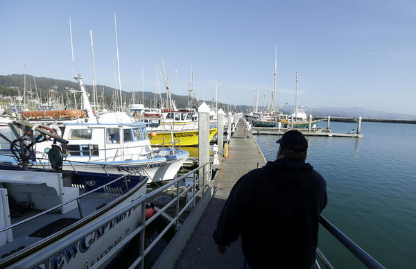 Geoff Bettencourt, owner of the fishing boat Moriah Lee, walks along a pier in Half Moon Bay, Calif.