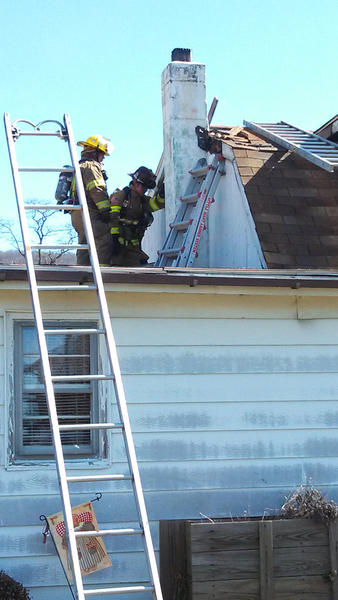 Firefighters work on the roof of a house on Locust Grove Road that was damaged in a fire Monday.