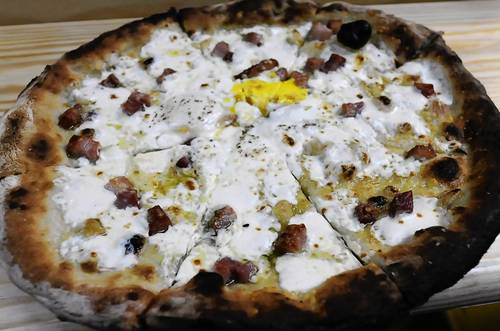 "The ""Sunny Side"" boasts fresh garlic, fresh mozzarella, parmesan pancetta, eggs, extra virgin olive oil and salt."