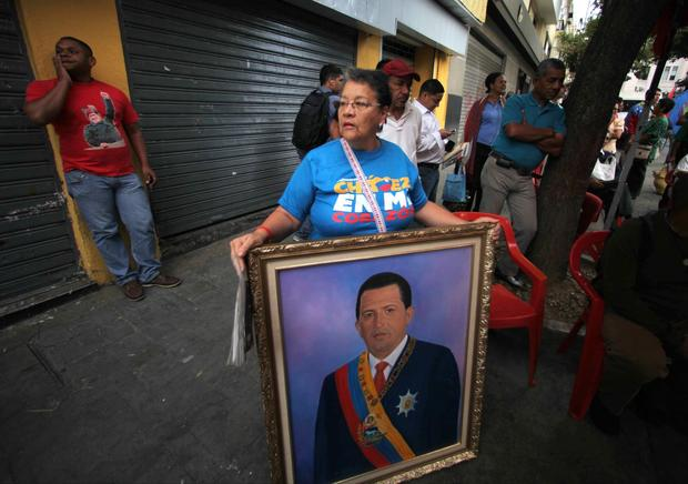 A woman holds a painting of President Hugo Chavez as supporters gather around Bolivar Square after his return to the country in Caracas.
