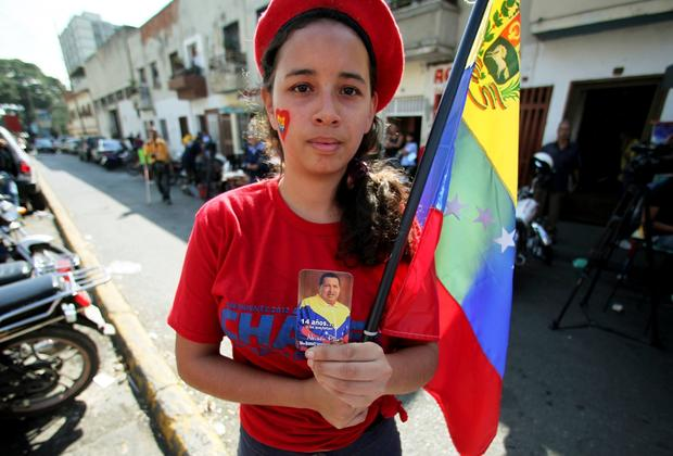 A supporter of Venezuela's President Hugo Chavez holds a photo of him as she celebrates his return, outside the Carlos Arvelo Military Hospital in Caracas.