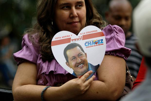 A supporter of Venezuela's President Hugo Chavez holds a heart-shaped placard with his image in Bolivar Square, where supporters gathered to celebrate his return, in Caracas.
