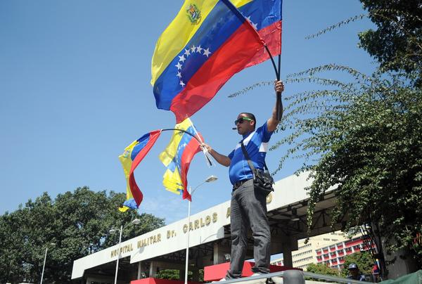 A vendor sells Venezuelan flags outside the military hospital in Caracas where Venezuelan President Hugo Chavez has been hospitalized following his return from Cuba.