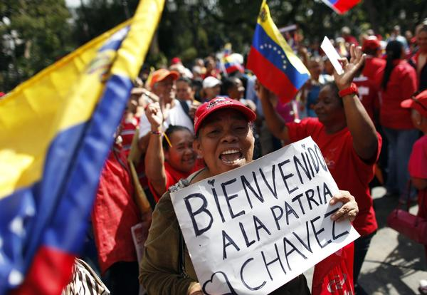 Supporters of Venezuelan President Hugo Chavez hold banners and shout slogans in Caracas on Monday as Chavez is reported to return to the country.