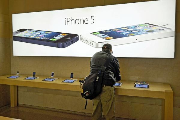 A customer at an Apple store in New York City tries out the company's iPhone 5. Proponents of phone unlocking have petitioned the White House for help obtaining a permanent exemption from copyright law for that purpose.