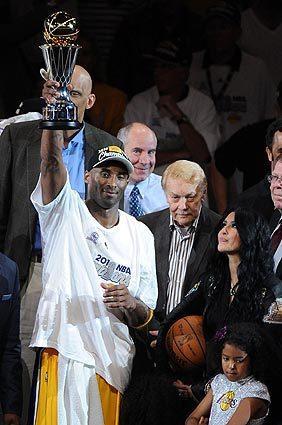 Jerry Buss, center, stands between Kobe and Vanessa Bryant after the Lakers defeated the Boston Celtics to win the NBA title in 2010. Kobe is holding up the trophy he won as series MVP.