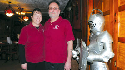 Kim and Denny Vought, owners of the Kings & Queens Restaurant & Pub, pose near a suit of armor inside the restaurant Feb. 13.