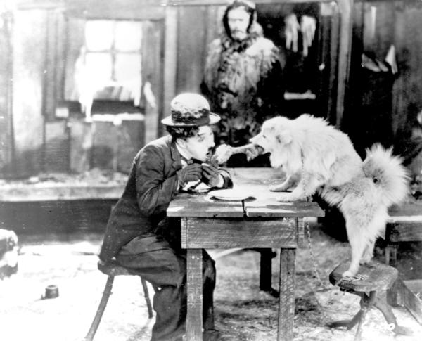 In a now-iconic scene, Chaplin's lonely prospector is throwing a New Year's Eve party. Unfortunately, it's getting late and his guests (a saloon girl he's fallen in love with and her friends) haven't shown up. The prospector begins to fantasize about the party he should be having and imagines the ladies coming to visit and having a grand old time. It's during this sequence that Chaplin performs the dinner roll routine in a scene that is comic but also a little heartbreaking when you remember that the prospector is doing this just to entertain his lonely self.