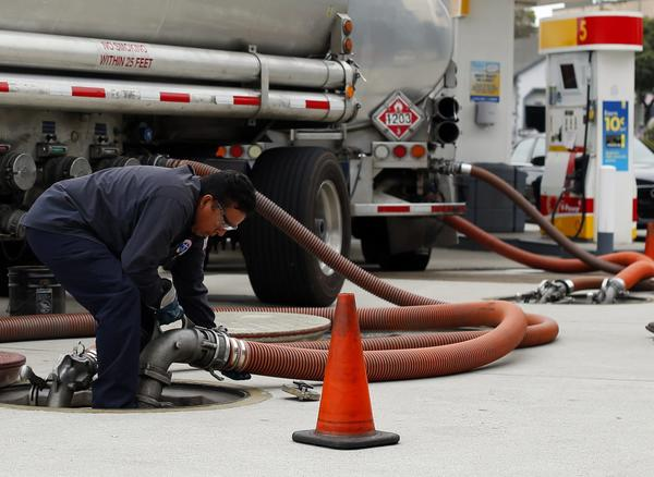 A worker delivers a new shipment of gasoline to a gas station in Encinitas, Calif. Some blame hedge funds that have been amassing winning bets on hundreds of millions of barrels of oil for the highest gasoline prices ever at this time of year.