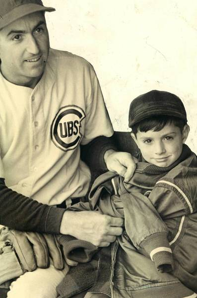 Cubs shortstop Len Merullo keeps his son, Len Jr., warm in the dugout at Wrigley Field in the 1940s. The ballpark looms large in the psyche of Cubs fans.