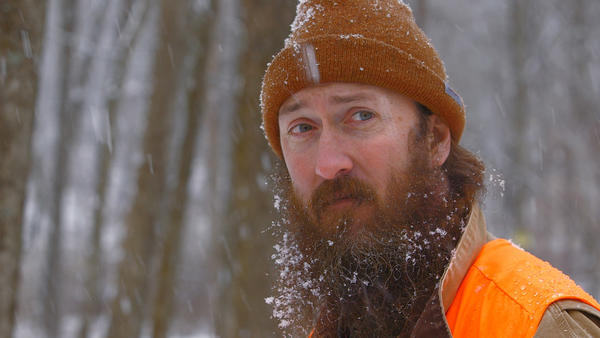 Aaron Cox walks through the woods on his Newtown property while hunting Jan. 28, 2013.