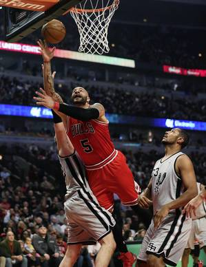 Carlos Boozer is fouled by the Spurs' Tiago Splitter on his way to the basket during the first half.