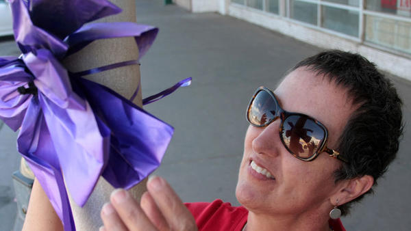Lorena Moreno ties a purple ribbon on a post during Calexico's Relay for Life's Paint the Town Purple on Second Street in Calexico on Monday.