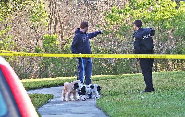 A resident chats with Orlando Police near the crime scene of a triple shooting early Tuesday morning.