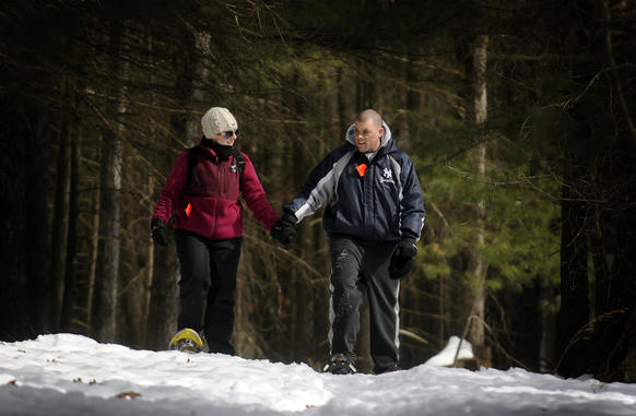 Lauren Killea and Steve Morehouse, both of South Windsor, hold hands in the woods at Windin