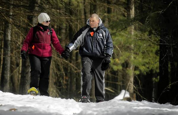 Lauren Killea and Steve Morehouse, both of South Windsor, hold hands as they walk through the woods while snowshoeing at Winding Trails in Farmington Sunday afternoon.