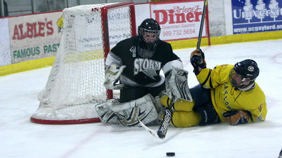 Gaylord senior Seth Muzyl slides in on the Mid-Michigan Storm goaltender during the Blue Devils' 4-0 victory Friday. Muzyl and the Blue Devils have now won three of their past five games.