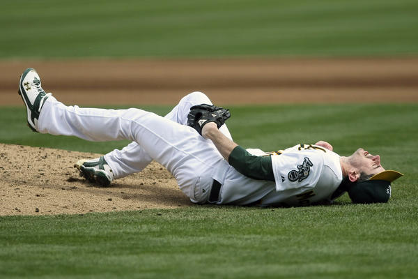 Brandon McCarthy (32) falls after being hit in the head on a line drive by Los Angeles Angels shortstop Erick Aybar (not pictured) while pitching for the Oakland A's.