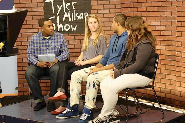 Tyler Milsap interviews guests on the set of his show.