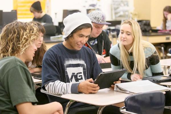Huntington Beach High's Ricky Berge, center, plays with his class-issued iPad as classmates Stephanie Hunt, right, and Aidan Abe, left, look on during a science class on Feb. 14.