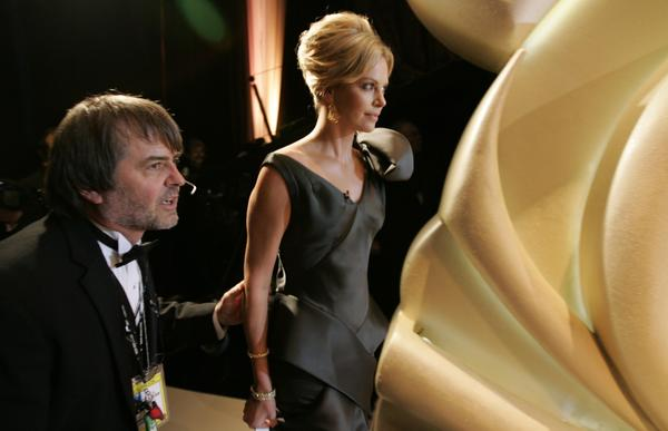 Charlize Theron gets the cue from Dency Nelson to walk onstage during the 78th Academy Awards in 2006.