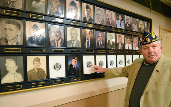 Hellertown American Legion Commander John Higginbotham looks at photos on the wall of previous Commanders. The Edward H. Ackerman American Legion Post on Main Street in Hellertown, which closed in 2008 due to cost of building upkeep and embezzlement,  reopens thanks to community volunteer effort.