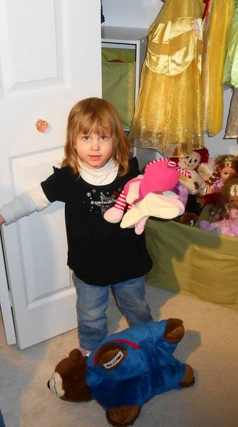 Evie Brown checks out her reorganized closet, complete with princess costumes and stuffed animals.