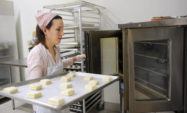 Nicole Campbell, of Durham and part of Crepe Crusaders Cafe takes biscuits out of the oven in the Artisan Kitchen that is located in Warm Sugar Bakery in Hellertown.