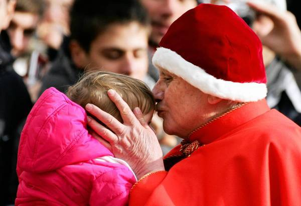 Pope Benedict XVI wears a camauro, a red velvet hat with white ermine trim, while kissing a baby at the Vatican in 2005.