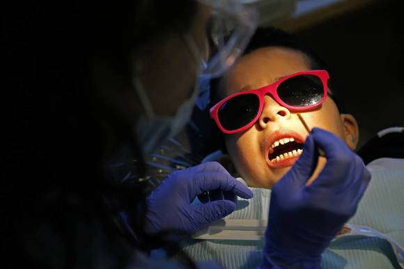 Jair Marquez Macias, 6, gets his teeth cleaned by dental assistant Faith Marren at Nathan Davis Elementary School in Chicago recently.