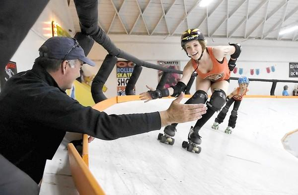 Jim O'Donnell, left, high-fives his daughter, a member of the OC Roller Girls junior team, as she skates by at halftime during a matchup with San Diego's Juvenile Dollinquents.