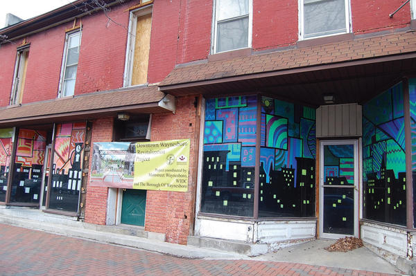 Waynesboro Area Senior High School students painted the windows at 27-29 E. Main St. to improve the building's aesthetics. Plans call for the structure to be demolished to make way for a plaza.